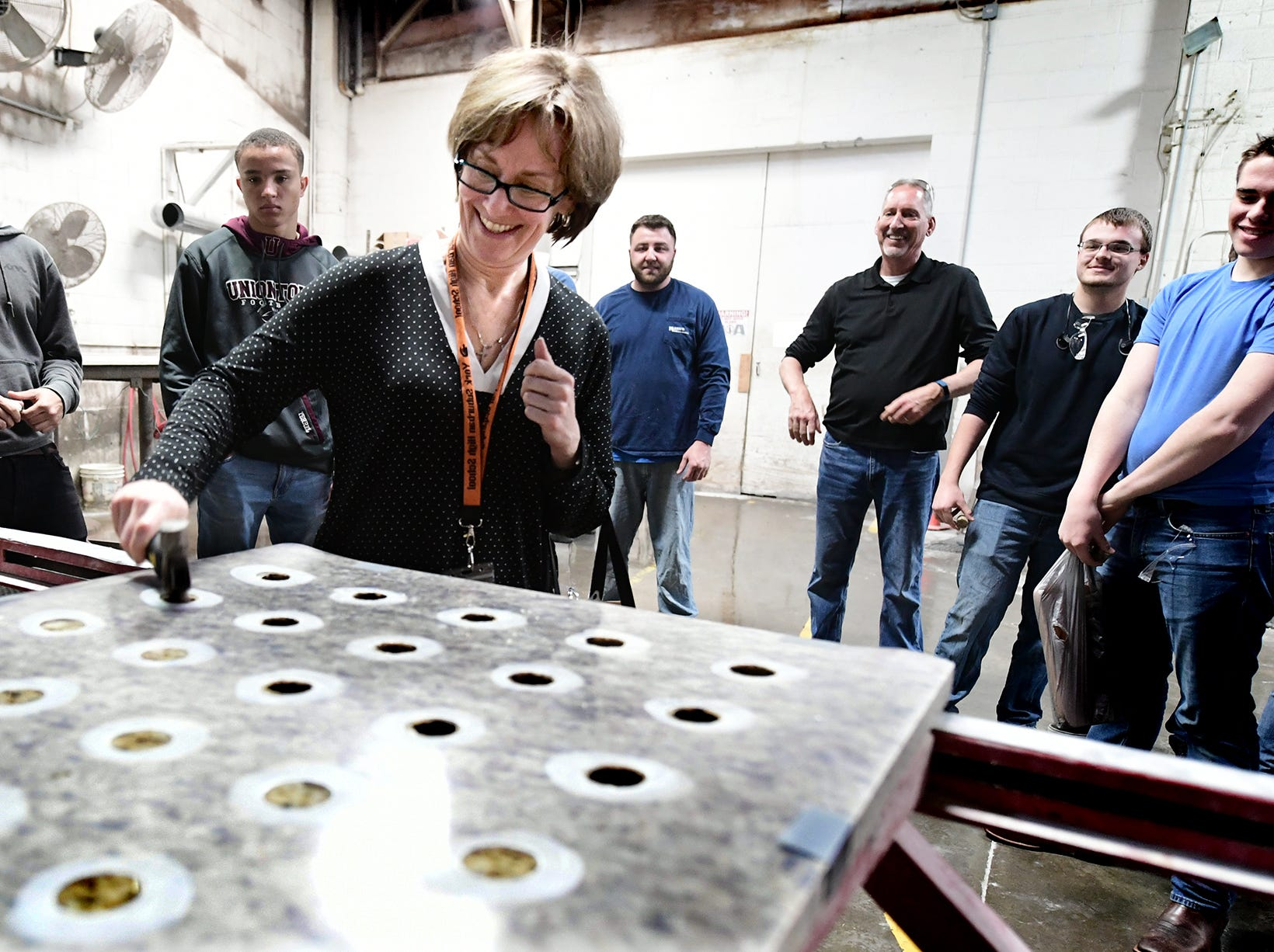 York Suburban High School guidance counselor Karen Forrer punches a spigot hole in a granite slab at Frank's Marble & Granite, in Red Lion, during the York Builders Association 2nd Annual Construction Career Day Monday, April 8, 2019. The goal of the program is to raise student-awareness about local career opportunities in the construction field. Association members host the students. The association has planned similar events at various companies through April 17. Nine area high schools are participating in the program, according to the builders association. Bill Kalina photo