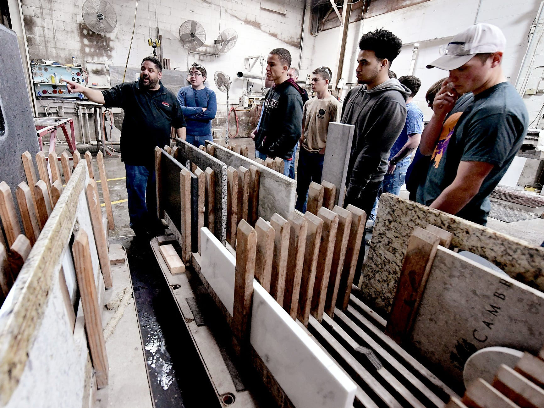 Frank's Marble & Granite owner Carmine Pantano, left, shows examples of products to students during a tour of the Red Lion business during the York Builders Association 2nd Annual Construction Career Day Monday, April 8, 2019. The goal of the program is to raise student-awareness about local career opportunities in the construction field. Association members host the students. The association has planned similar events at various companies through April 17. Nine area high schools are participating in the program, according to the builders association. Bill Kalina photo