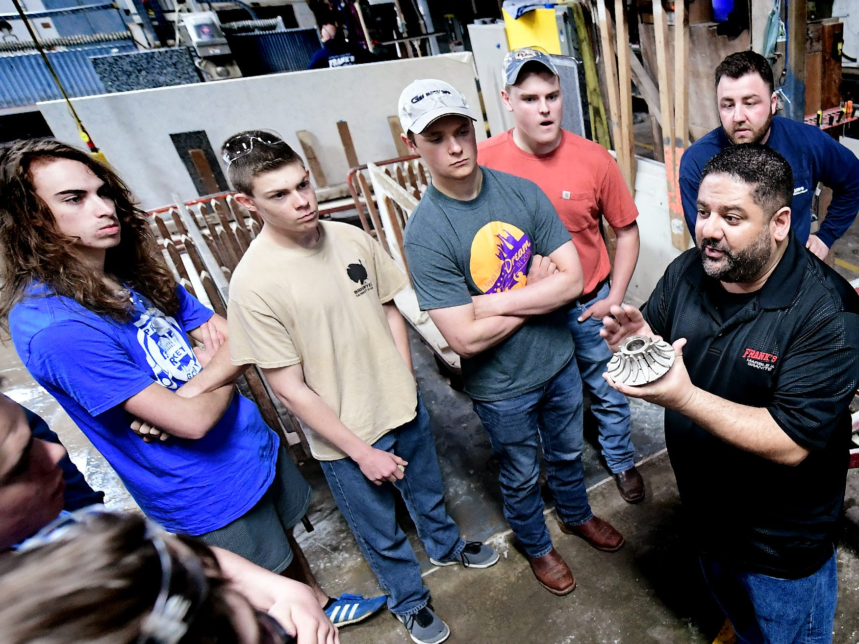 Frank's Marble & Granite owner Carmine Pantano shows a diamond router bit to students during a tour of the Red Lion business during the York Builders Association 2nd Annual Construction Career Day Monday, April 8, 2019. The goal of the program is to raise student-awareness about local career opportunities in the construction field. Association members host the students. The association has planned similar events at various companies through April 17. Nine area high schools are participating in the program, according to the builders association. Bill Kalina photo