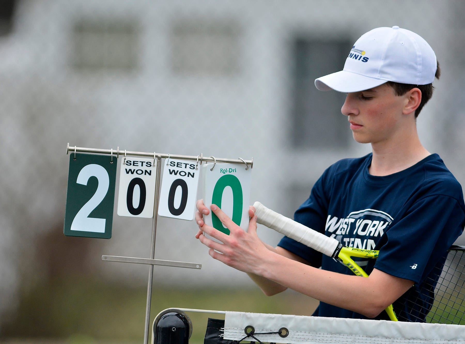 West York's Augie Citrone changes the score cards while playing Josh Lynn of Hanover in the number one seed match, Monday, April 8, 2019.
