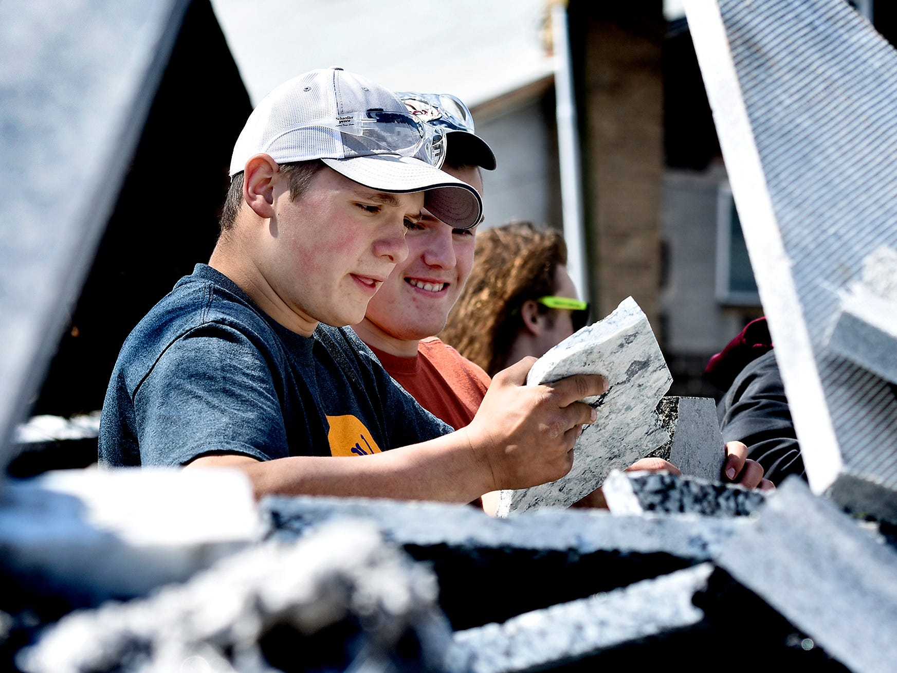 Spring Grove High School juniors Sam Parr, left, and Mason Pflueger rummage for marble scraps at Frank's Marble & Granite, in Red Lion, during the York Builders Association 2nd Annual Construction Career Day Monday, April 8, 2019. The goal of the program is to raise student-awareness about local career opportunities in the construction field. Association members host the students. The association has planned similar events at various companies through April 17. Nine area high schools are participating in the program, according to the builders association. Bill Kalina photo