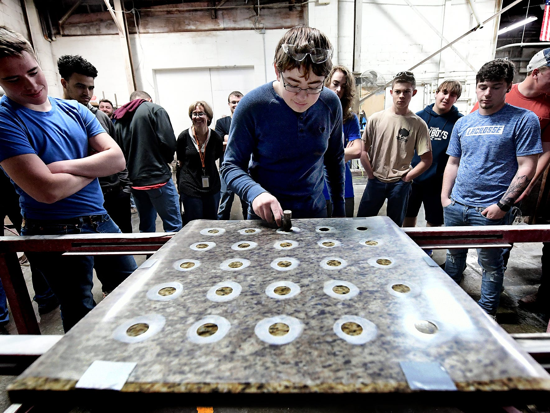 York Suburban High School junior Drew Davis punches a spigot hole in a granite slab at Frank's Marble & Granite, in Red Lion, during the York Builders Association 2nd Annual Construction Career Day Monday, April 8, 2019. The goal of the program is to raise student-awareness about local career opportunities in the construction field. Association members host the students. The association has planned similar events at various companies through April 17. Nine area high schools are participating in the program, according to the builders association. Bill Kalina photo