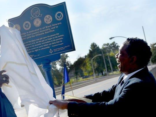 Master Sgt. Retired Lance Burke unveils a marker, part of the South Penn Street bridge dedication to black veterans.