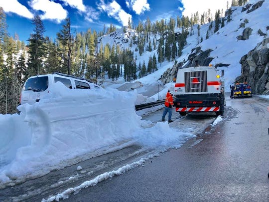 A Caltrans blower removes snow from around a partially buried Nissan Xterra that was caught in an avalanche on U.S. 50 on Sunday, April 7.