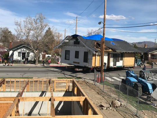 The 1908 Humphrey House from UNR's Gateway District is backed into its new site at 655 S. Arlington Ave. in Old Southwest Reno on April 7, 2019. The house will be lifted onto the array of support beams (lower left), then arranged into final position.