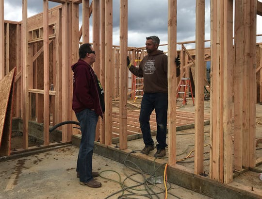 Homeowner Randy Ledbetter Sr., left, talks to contractor Aaron Jones as crews work to rebuild Ledbetter's home in Lake Keswick Estates.