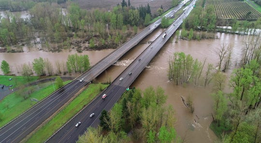 The Santiam River flows over its banks under the Interstate 5 overpass at the Santiam rest area as the river reached minor flood stage at 15.22 feet in Jefferson Monday afternoon following several days of heavy rain.