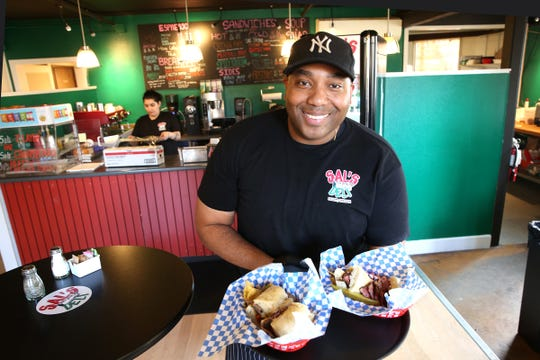 Owner Aaron Heath poses with two of his signature sandwiches at Sal's Deli in Salem on April 5, 2019.