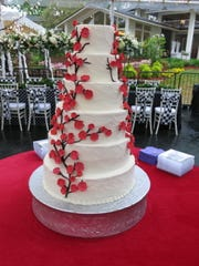 The bride's cake by Sweetie Cakes, of Benton,  at the Thompson-Murphy wedding reception, featured confection cherry blossoms climbing up the six layers. Bride Carolyn P. Murphy carrieda  hand-tied bridal bouquet that included blooming cherry blossoms, pulling in a thoughts of a honeymoon to China