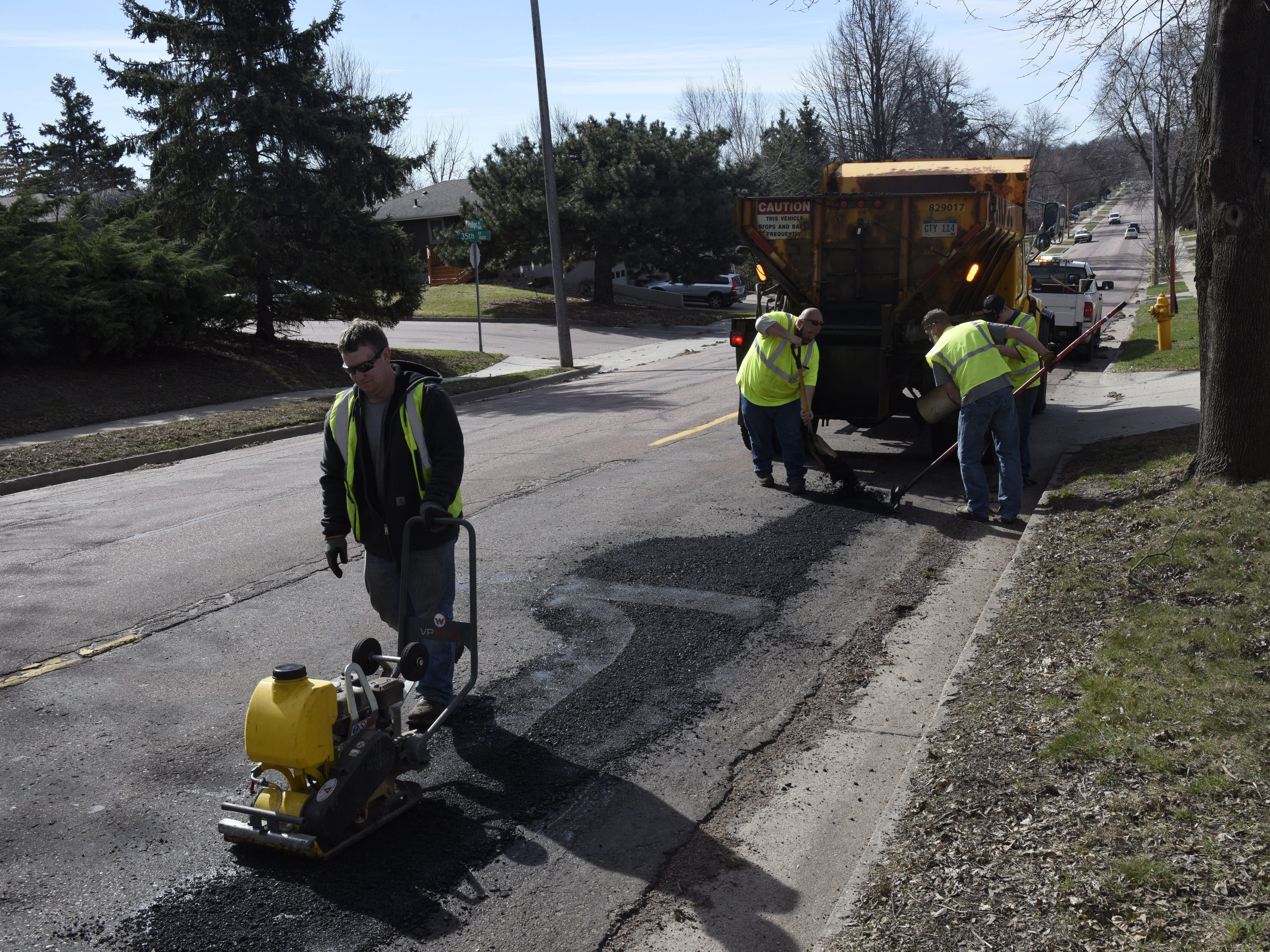 Mike O'Kane operates a vibratory plate compactor while Erik Harrington, Chad Sundvold and Reece Cunningham smooth out asphalt.