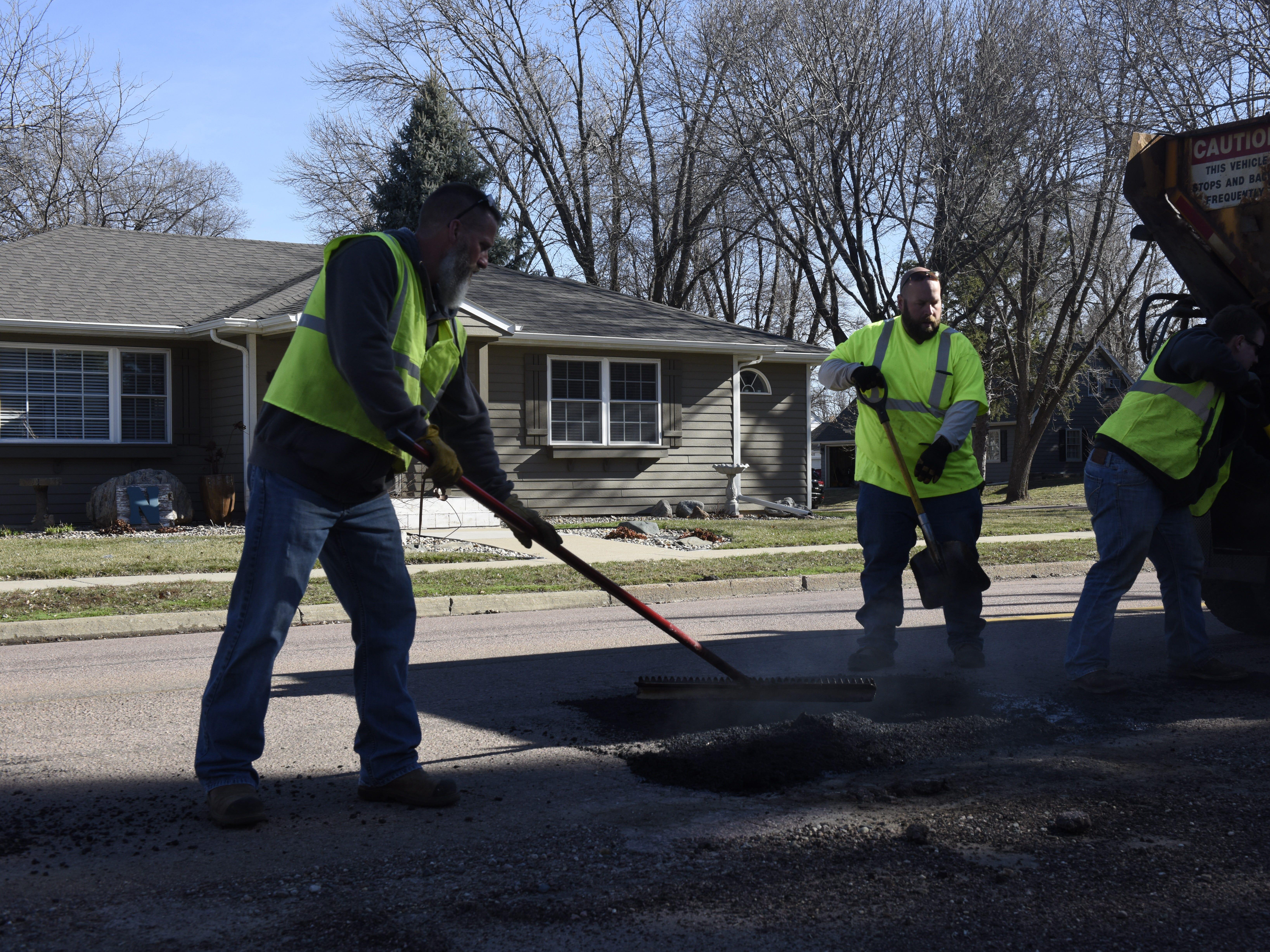 Chad Sundvold, Erik Harrington and Mike O'Kane repair a road on April 8.