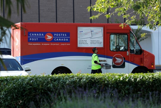 In this Sept. 26, 2018 photo, a Canadian postal worker walks to his truck. Canada's approach to legal marijuana permits postal delivery of cannabis. Missouri's approach to medical marijuana would rely on state-licensed transport companies using unmarked vehicles.