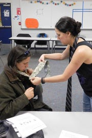 Sierra Service helps a theater tech student tie a four-in-hand knot.