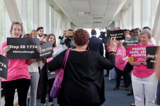 In an April 8, 2019, photo, Florida National Organization for Women (NOW) activist Barbara DeVane waves to Planned Parenthood and Floridians for Reproductive Freedom protestors as they protest Senate Bill 1774 before it is heard in a Senate Health Policy Committee meeting.