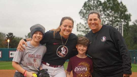 Hayden Stone (left) and her brother Harrison with FSU head coach Lonni Alameda and catcher Anna Shelnutt.