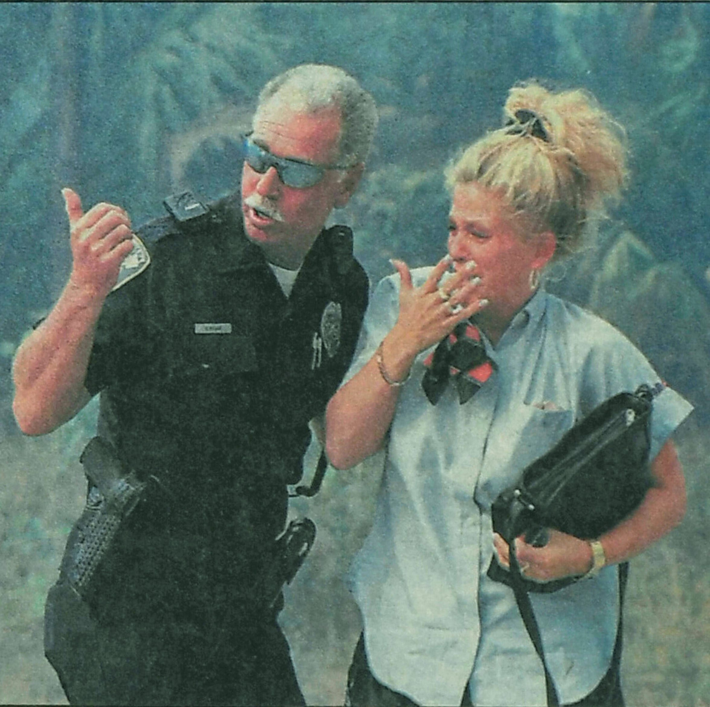 Port St. Lucie Police Officer Brian Major offers comfort to a resident after her neighborhood near Southwest Deckard Street and Southwest Abingdon Avenue was evacuated on April 15, 1999, in Port St. Lucie. Dozens of homes were destroyed in the area that day.