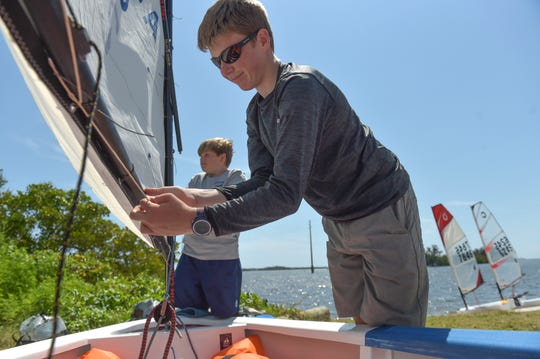 """Shae Riley, 14 (front), sets the rigging for the sail of his Optimist sailboat with the help of Michael Ladd, 11, both with the Youth Sailing Foundation of Indian River County, as Shae prepares for competing in the Youth Sailing Foundation's Steve Martin Memorial Regatta on Sunday, April 7, 2019, at the southwest corner of the Alma Lee Loy (17th Street) Bridge in Vero Beach. """"I like the water and just sailing,"""" Shae Riley said. """"It's going to be fun, It's hometown so I've go to do good and I just hope I have a good time out there.""""  CQ: Shae Riley, Michael Ladd, Optimist sailboat Alma Lee Loy Bridge, Steve Martin"""