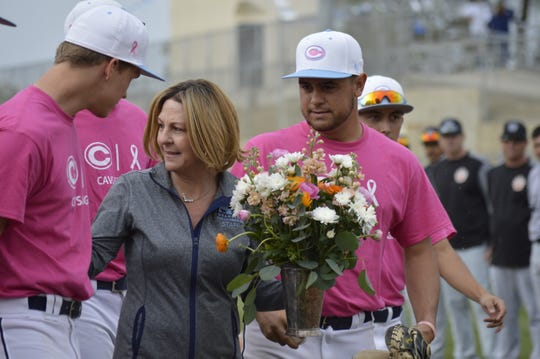 Stacey Marshall is handed a bouquet of flowers on April 5 during CVC's cancer awareness game. Marshall, who was diagnosed with cancer in December 2018, is the mother CVC baseball coach Shane Marshall.