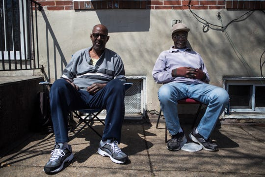 "Brothers Leon and Franklin West relax near the corner of East 9th and Pine streets Monday afternoon. Both men were not outside when six people were shot on Pine Street Sunday night. ""I'm like a cowboy, I don't come out after sundown,"" Leon West said."