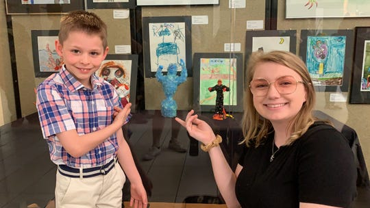 Artists Aiden O'Malley and Freshman MSU art major Kristen Longo in front of their works at the Art Relay Gallery exhibition on display through April in Sikes Senter Mall.