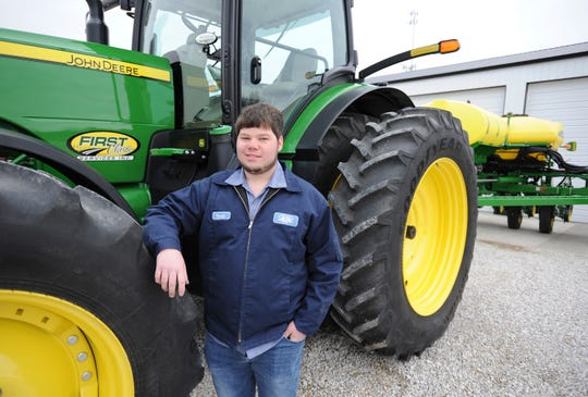 In this March 14, 2019 photo, Tanner Stroup stands by his John Deere 8400 R tractor on his farm in Maceo, Ky. At age 24, Stroup is bringing youth to an otherwise aging profession.  According to the USDA's Census of Agriculture, the average age of a Kentucky farmer is 57.6 years old while the U.S. average is 58.3 years old.