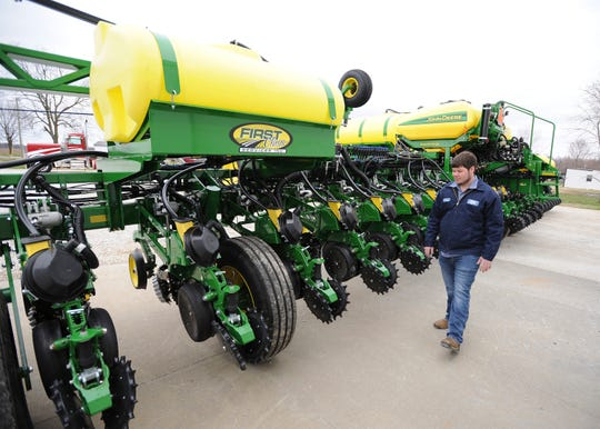 In this March 14, 2019 photo, Tanner Stroup checks his 24-row, high-speed 1775 NT planter in preparations for spring planting on his farm in Maceo, Ky.  At age 24, Stroup is bringing youth to an otherwise aging profession.  According to the USDA's Census of Agriculture, the average age of a Kentucky farmer is 57.6 years old while the U.S. average is 58.3 years old.