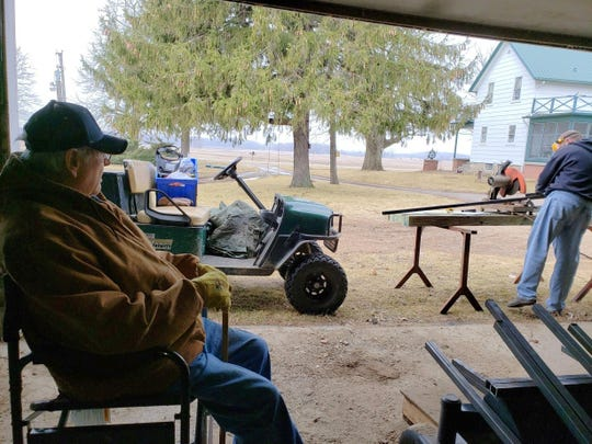 Bob watches as son, Russ, works on making modifications to make Bob's for lawnmower more accessible.