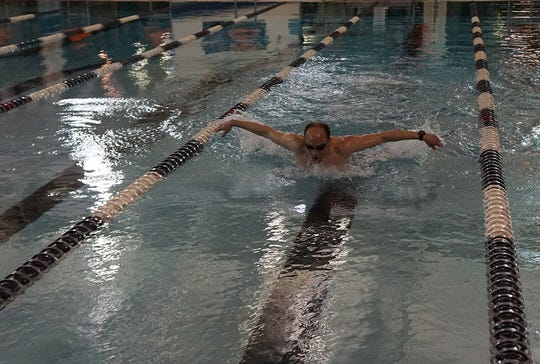 Brad Hollingsworth spends his early morning hours training at the Muskingum Recreation Center pool in training for the Ironman Florida competition. He is participating in the Olympic distance race in memory of his friend and training partner, Brenda Hoffman who was killed four years ago while the two were on a training ride.