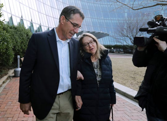 Former Texas men's tennis coach Michael Center, left, departs federal court in Boston with an unidentified woman on March 28.