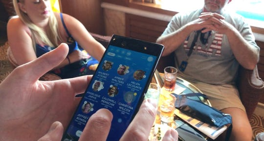Waiter uses OceanMedallion to take drink orders and identify passengers on board the Caribbean Princess cruise ship.