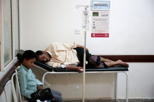 In this July 1, 2017 file photo, a man is treated for suspected cholera infection at a hospital in Sanaa, Yemen. An Associated Press investigation finds that the massive cholera epidemic was aggravated by corruption and official intransigence. The investigation has found that both the Iranian-backed Houthis rebels and their main adversary in the war -- the U.S.- and Saudi-backed government that controls southern Yemen -- impeded efforts by relief groups to stem the epidemic.