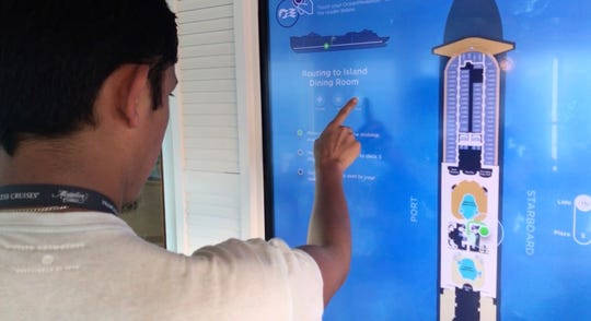 A passenger uses the touchscreen to find his way around the ship.
