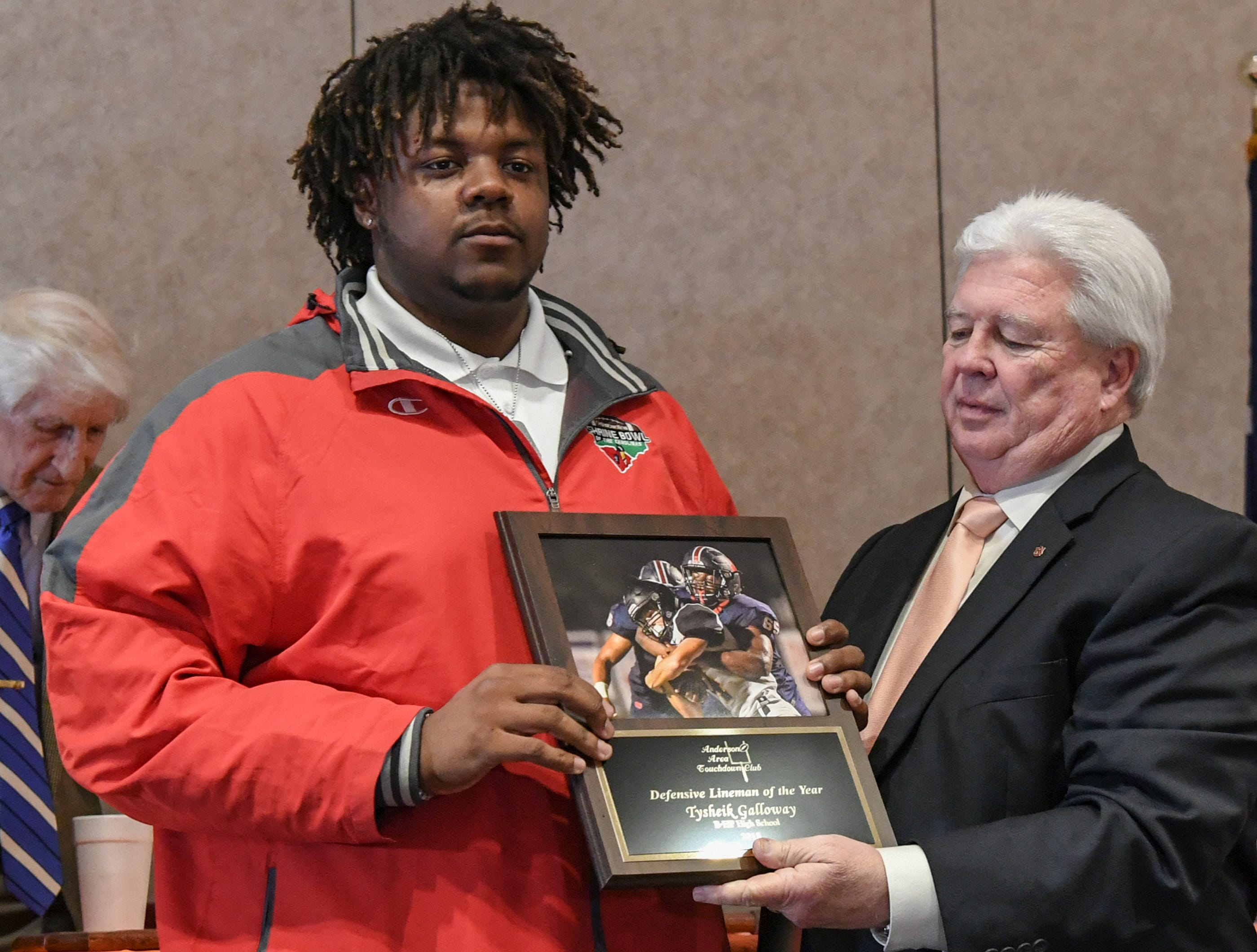 Tysheik Galloway, left, defensive lineman of the year from Belton-Honea Path High School accepts his award from Dick Smith, right, during the Anderson Area Touchdown Club Annual Awards Banquet at the Anderson County Civic Center Monday, April 8th, 2019.