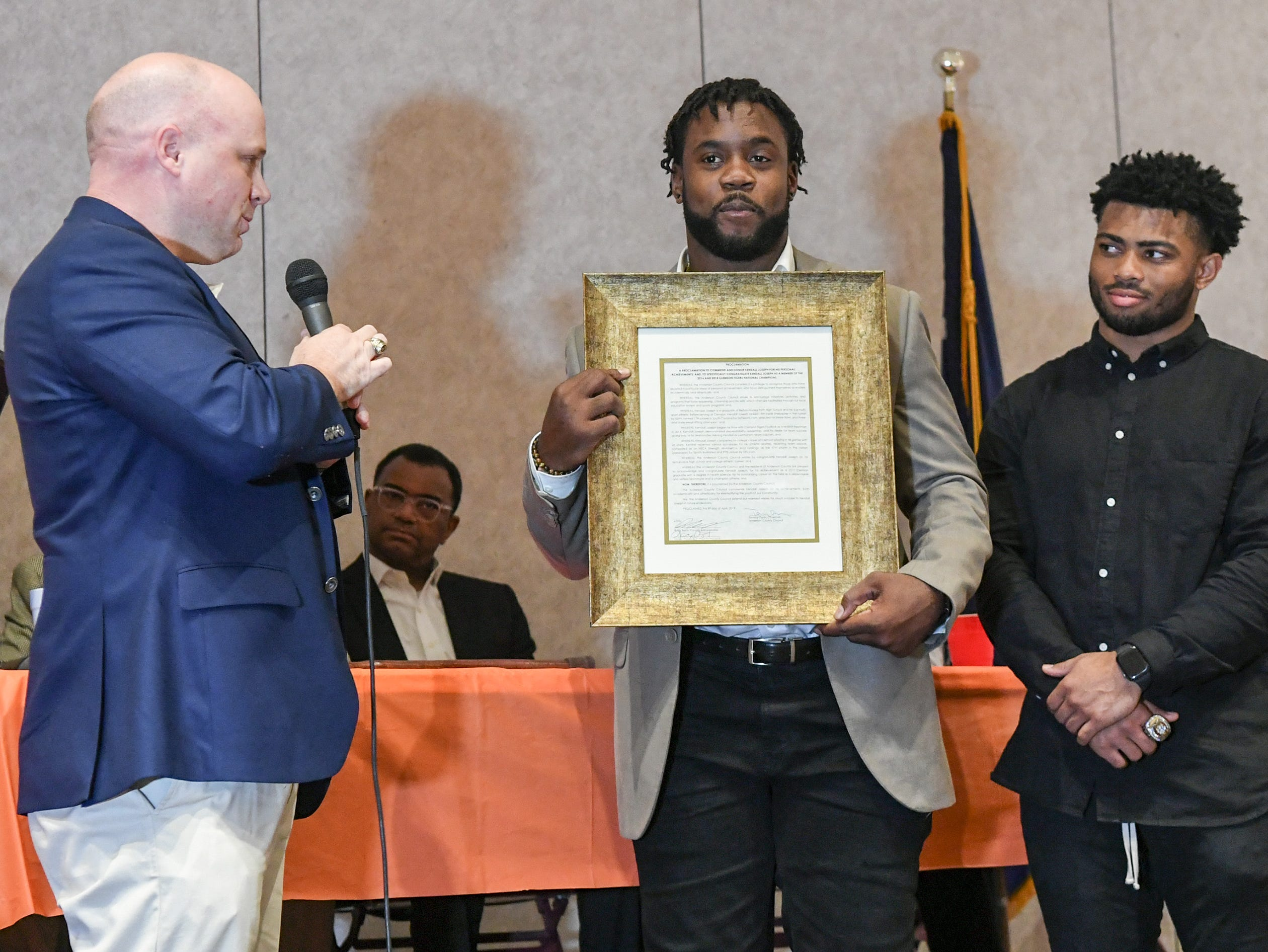 Craig Wooten, left, Anderson County Councilman makes a proclamation honoring Kendall Joseph, middle, a former Belton-Honea Path High School football player from Anderson County, and two-time college football national champion  during the Anderson Area Touchdown Club Annual Awards Banquet at the Anderson County Civic Center Monday, April 8th, 2019. Darien Rencher, right, former T.L. Hanna High player, was honored later by councilman Brett Sanders.