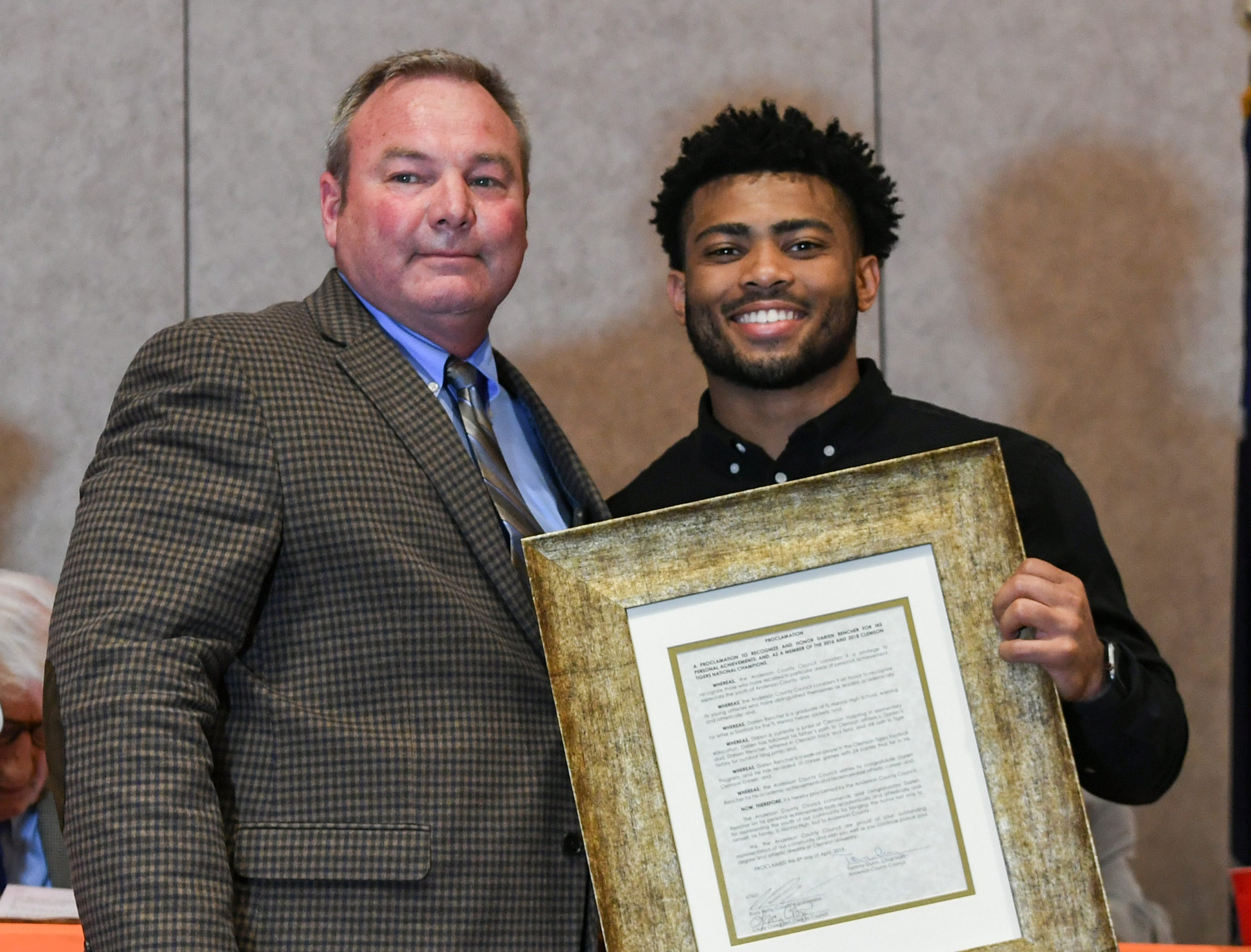 Brett Sanders, left, Anderson County Councilman makes a proclamation honoring Darien Rencher, right, a former T.L. Hanna High football player from Anderson County, and two-time college football national champion during the Anderson Area Touchdown Club Annual Awards Banquet at the Anderson County Civic Center Monday, April 8th, 2019.