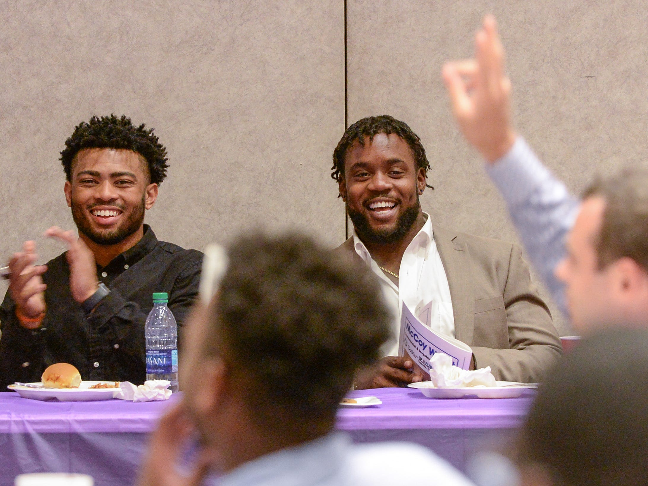 Darien Rencher, left, Clemson football running back and former T.L. Hanna High School, smiles with Kendall Joseph, former Belton-Honea Path and both two-time college football national champions, as Hunter Renfrow raises his hand during the Anderson Area Touchdown Club Annual Awards Banquet at the Anderson County Civic Center Monday, April 8th, 2019.