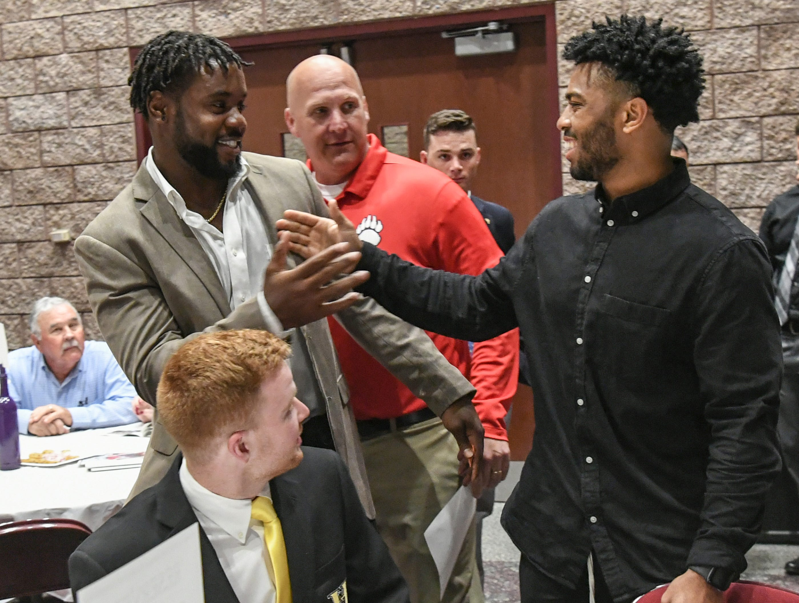 Kendall Joseph, left, former BHP and Clemson star, greets Darien Rencher, right, former T.L. Hanna and current Clemson running back, as Russell Blackston, middle, watches with Alex Meredith, below, during the Anderson Area Touchdown Club Annual Awards Banquet at the Anderson County Civic Center Monday, April 8th, 2019. Awards were given to the Players of the Year and the Coach of the Year from the eight Anderson County high schools. The club honored former Belton-Honea Path player Kendall Joseph who was part of two National Championship Clemson football teams.