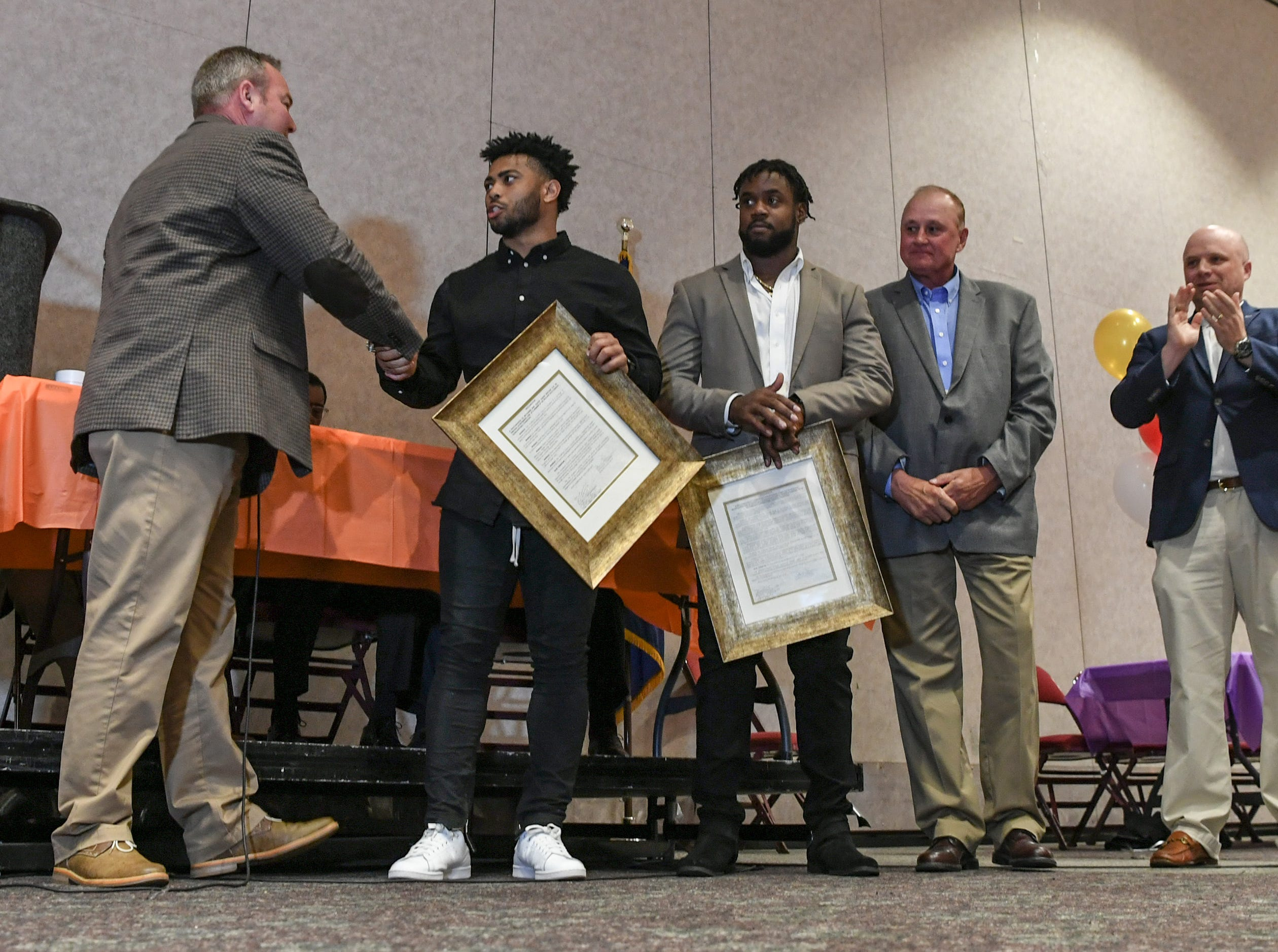Brett Sanders, left, Anderson County Councilman makes a proclamation honoring Darien Rencher, middle, a former T.L. Hanna High football player from Anderson County, and two-time college football national champion during the Anderson Area Touchdown Club Annual Awards Banquet at the Anderson County Civic Center Monday, April 8th, 2019. Craig Wooten honored Kendall Joseph, right, a former Belton-Honea Path High School player earlier.