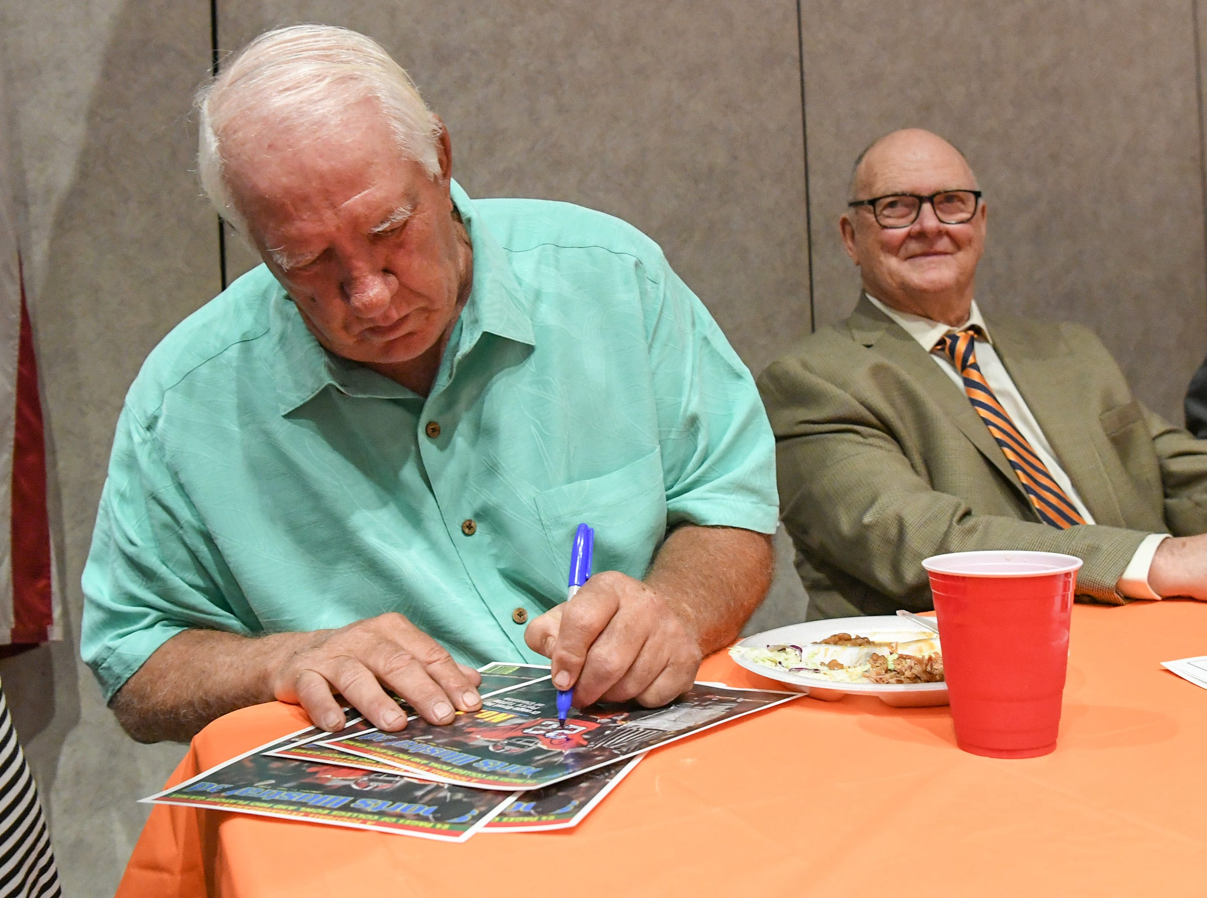 Former Clemson football coach Danny Ford signs an autograph before the Anderson Area Touchdown Club Annual Awards Banquet at the Anderson County Civic Center Monday, April 8th, 2019.