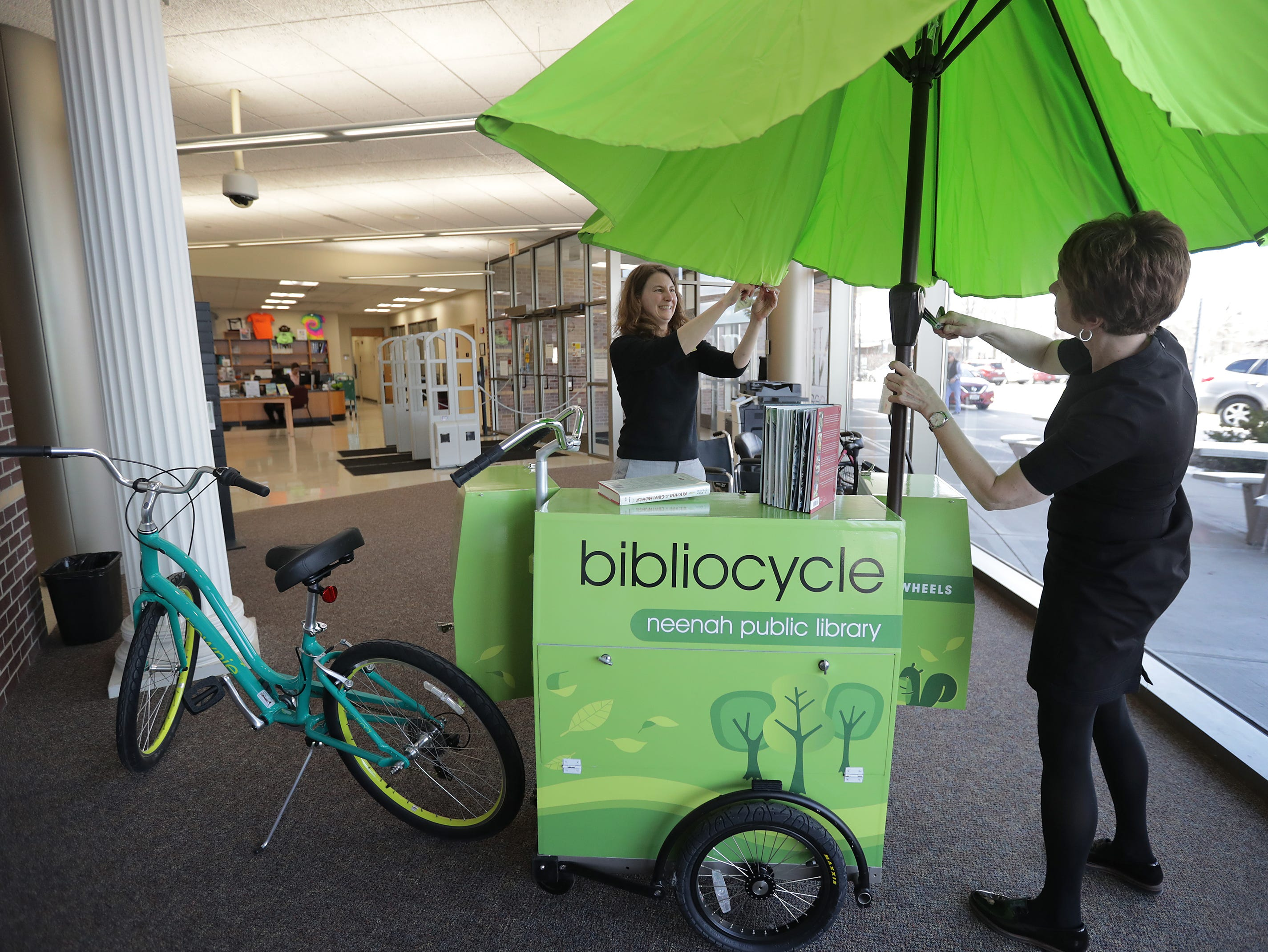 Library Director Gretchen Raab, right, and assistant library director Nicole Hardina-Wilhelmand sets up a display featuring the Neenah Public Library Bibliocycle on Wednesday, April 3, 2019, in Neenah, Wis. It's a bicycle with a cart containing books, and it functions as mobile mini library. Staff will take it to apartments and parks, as weather permits, allowing patrons to check out materials on the spot.Wm. Glasheen/USA TODAY NETWORK-Wisconsin.