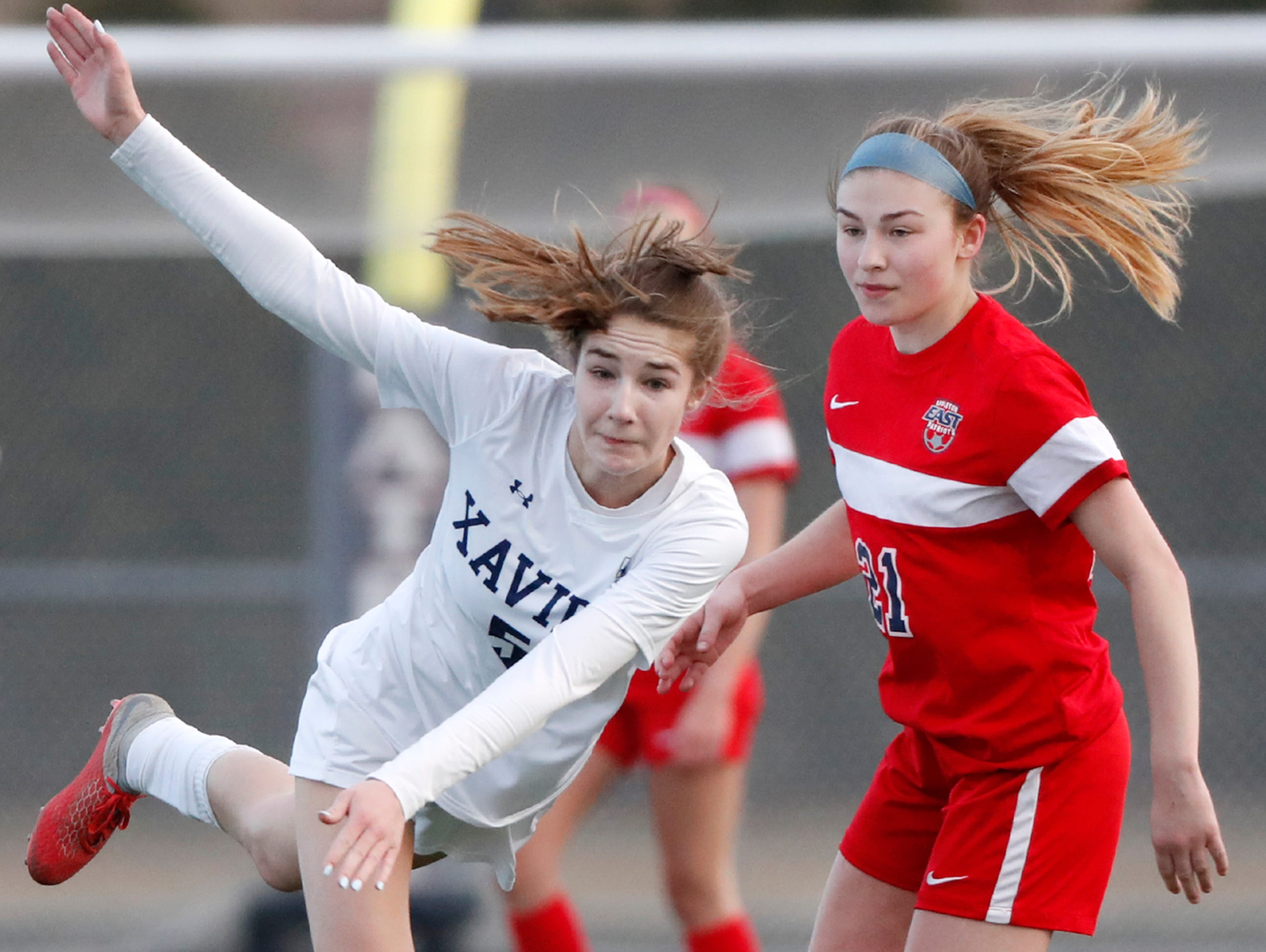 Xavier High School's Anna Rose Van Ye tries to regain her footing after getting past Appleton East High SchoolÕs Baylee Ahrens Friday, April 5, 2019, in Appleton, Wis. Danny Damiani/USA TODAY NETWORK-Wisconsin