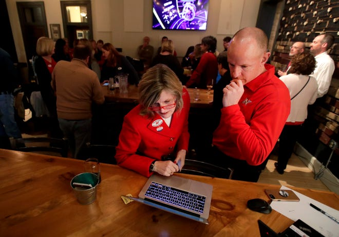 Neenah District Administrator Mary Pfeiffer and communications manager Jim Strick monitor the April 2 referendum results at Lion's Tail Brewing Co. in Neenah.