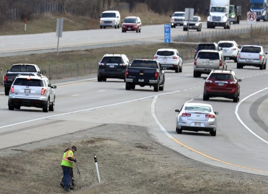 An Outagamie County worker picks up litter Tuesday near the on-ramp to northbound Interstate 41 at Richmond Street in Appleton.