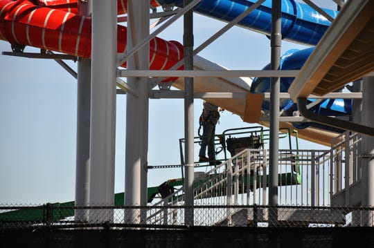 A worker installs a section of a new, red water slide at Adventure Cove at Rose Park on Tuesday.