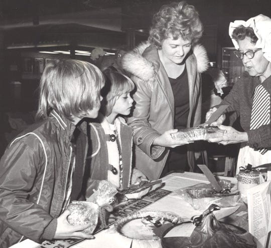 Scott (from left), 9, Martha, 7, and Mrs. David Girdner show their selection of goodies to AAUW member Mrs. Clay Randel years ago.