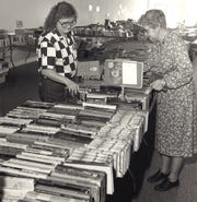 Sandra Trosky, AAUW book sale chairwoman, and helper Laurie Dudley prepare books for the organization's annual sale in November 1986.