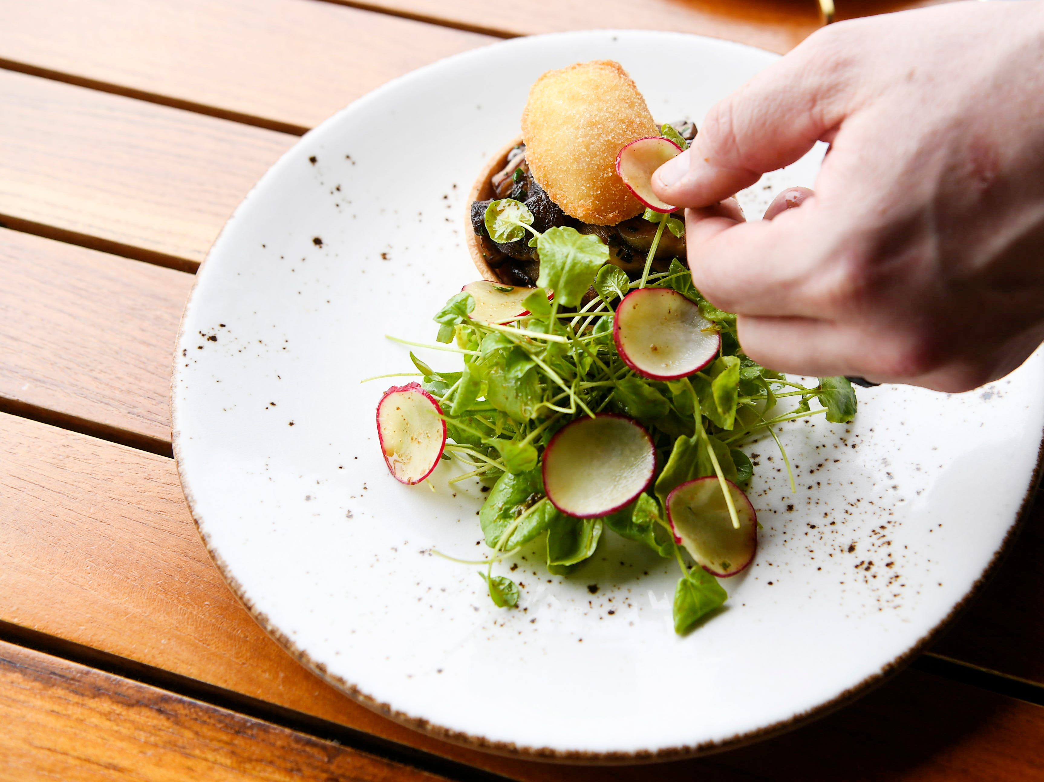 Edison Craft Ales and Kitchen executive chef Richard Gras adds finishing touches to a wild mushroom tart at the Grove Park Inn April 4, 2019.