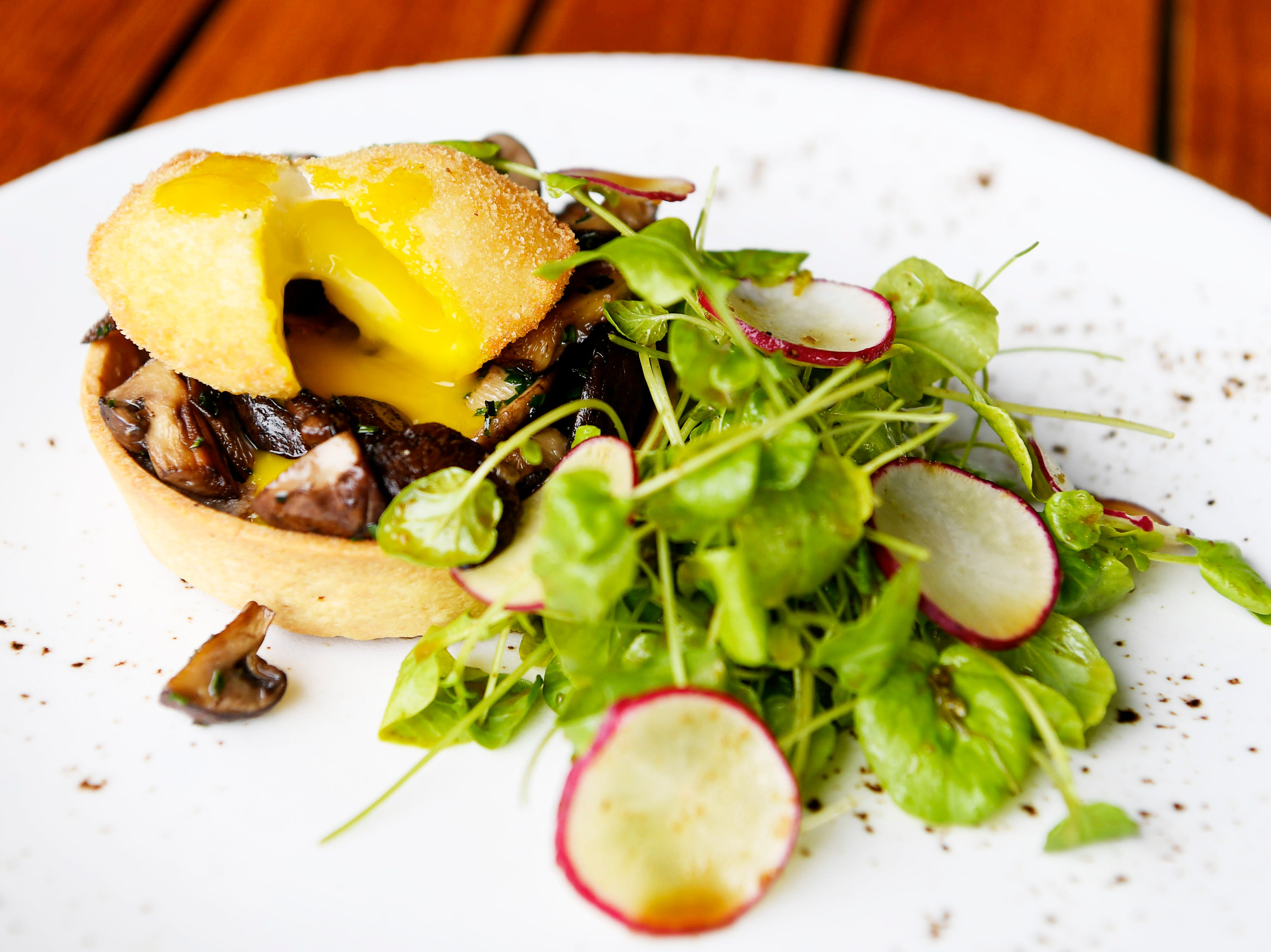 A wild mushroom tart with a poached egg and a side oflong-stemmed watercress and radishes at Edison Craft Ales and Kitchen in Asheville April 4, 2019.