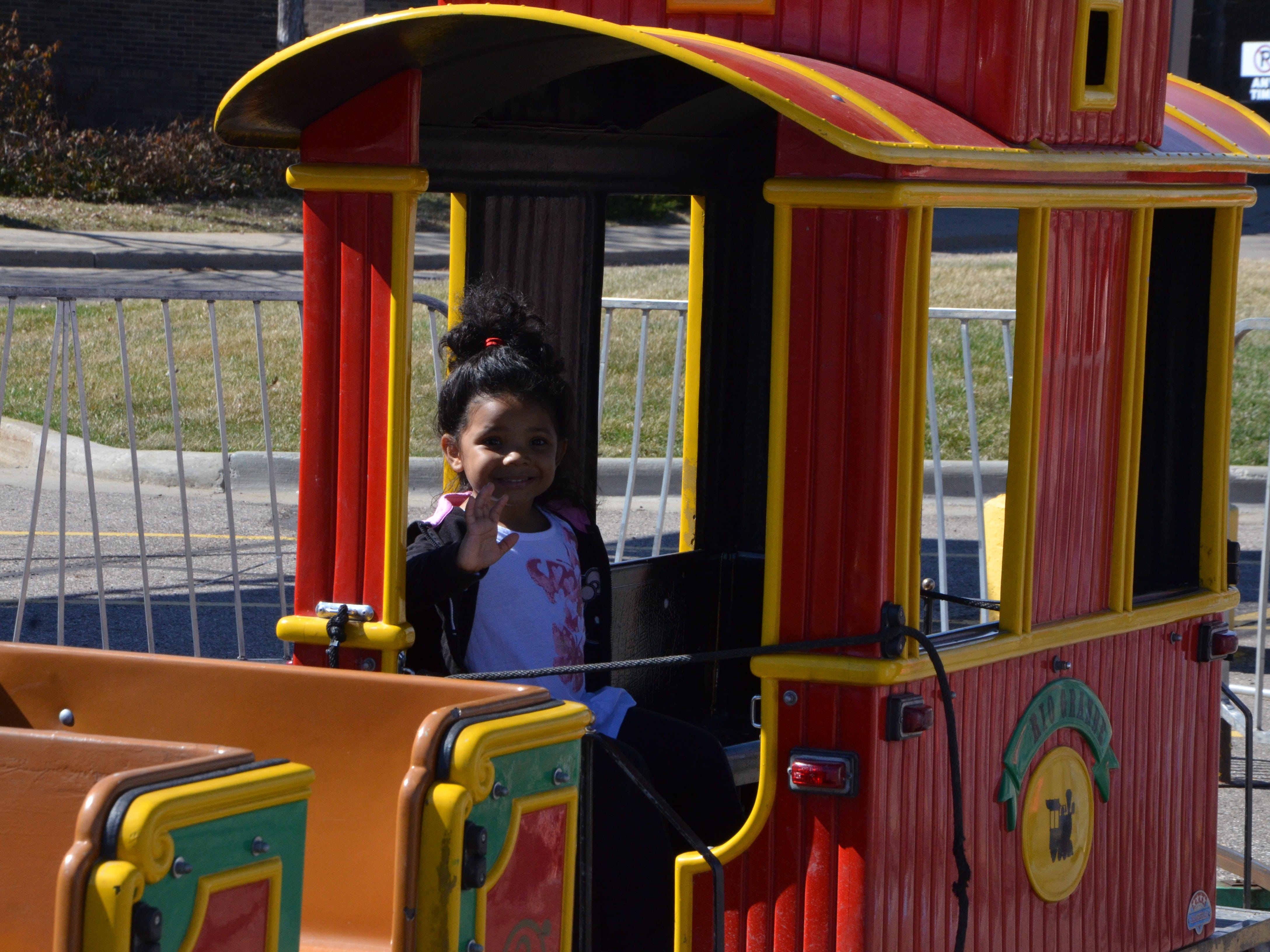 Alanna Williams, 3, rides the miniature train at the Family Fun Tyme Amusements in the parking lot of Lakeview Square Mall on Monday, April 8, 2019.
