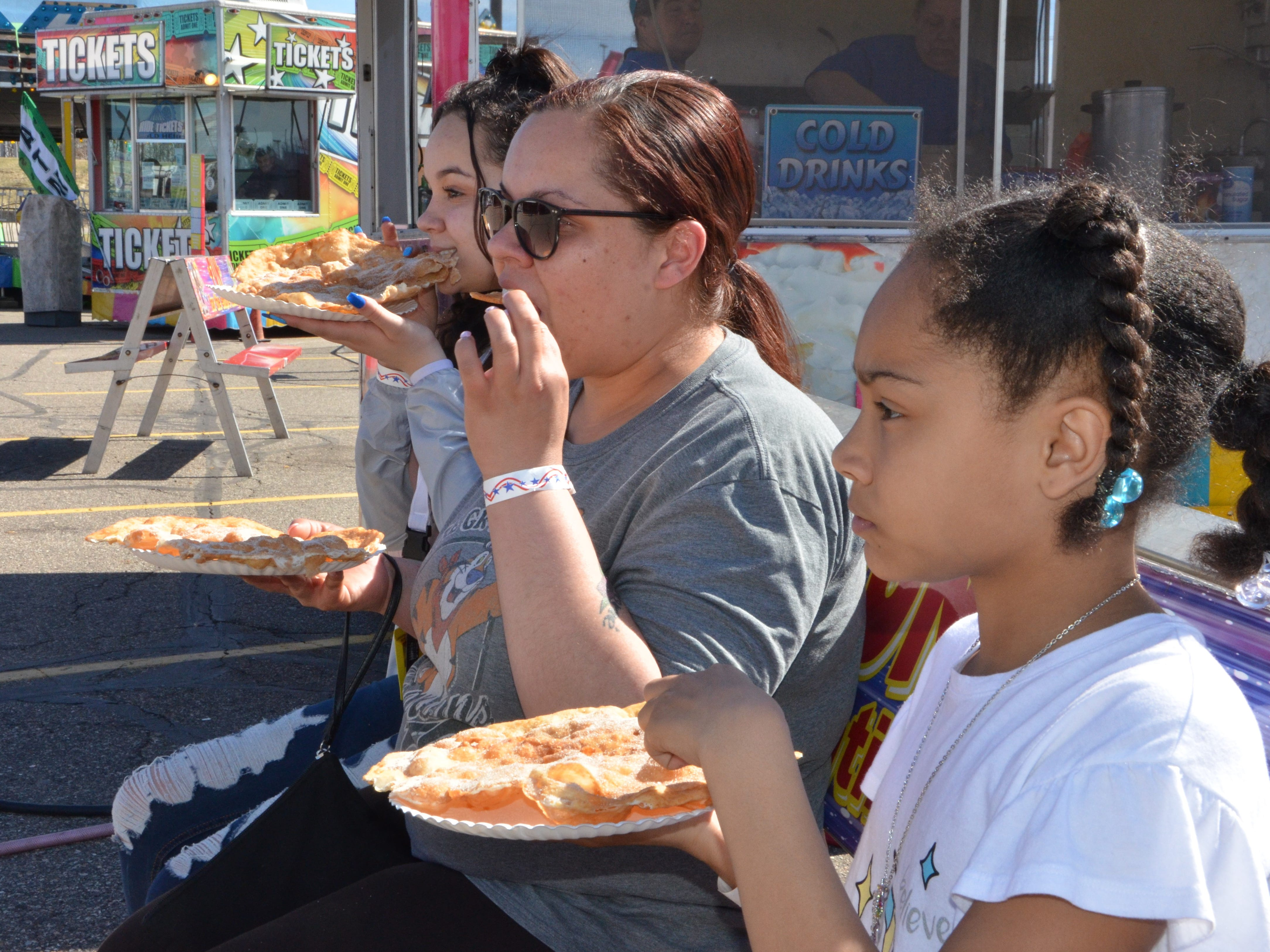 (L-R) Dan'nica Phelps, Teone Phelps and Kamone Phelps enjoy elephant ears on a bench at the Family Fun Tyme Amusements in the parking lot of Lakeview Square Mall.